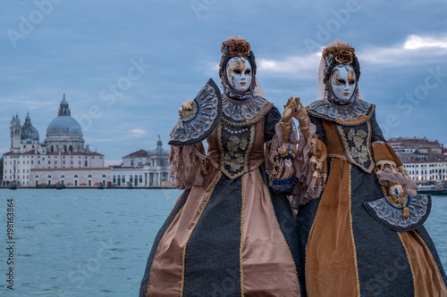 Two women in traditional costumes standing in front of the the Grand Canal during the Venice Carnival Canvas-taulu