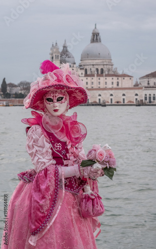 Valokuva Woman in traditional costume and mask standing in front of the the Grand Canal during the Venice Carnival
