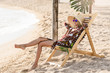 woman in hat rests in chaise longue on the beach