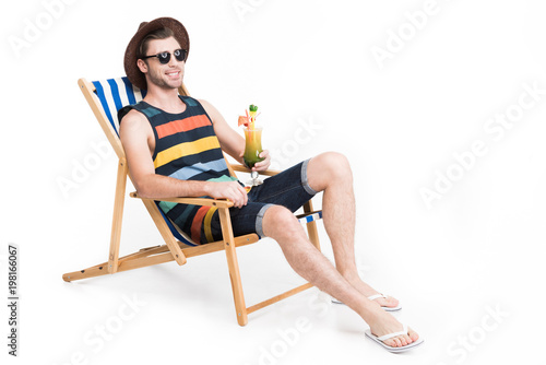 Photo handsome man in sunglasses and hat relaxing on beach chair with cocktail, isolat