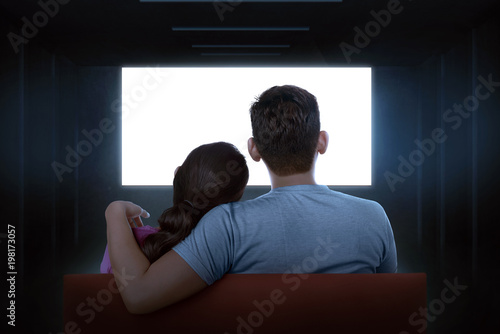 Portrait of asian couple sitting on couch watching blank tv