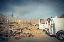 Construction Work Van With Door Open In The Back And Working Tools Inside Near Construction Site. Wood Frame House Project Foundation Framing In Irving, Texas, USA.