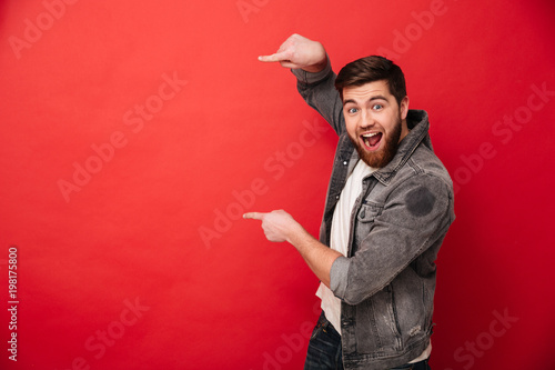 Photo of agitated man wih beard in casual clothing pointing fingers on copyspace Canvas Print