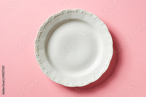 White plate on pink background, from above
