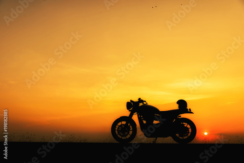 Fotografía  Silhouette of motorcycle parking with sunset background in Thailand,Young Traveller man place helmet on motorbike