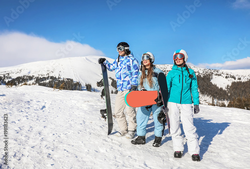 Fotografering Group of snowboarders on ski piste at snowy resort