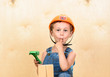 Kid boy as funny builder holding finger in mouth after hitting it with hammer