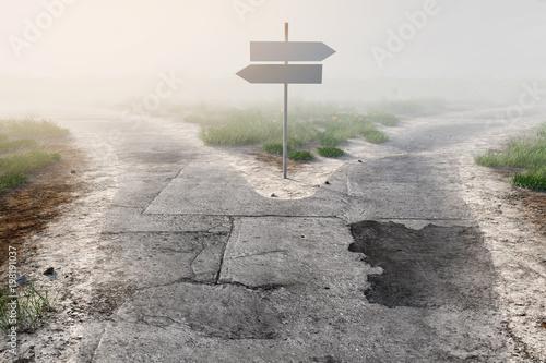 Wegweiser an Weggabelung im Nebel Fototapete