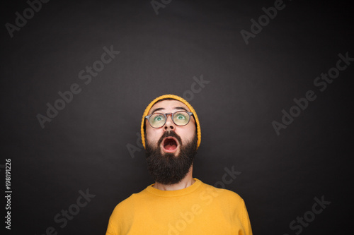 Shocked hipster looking up on black Canvas Print