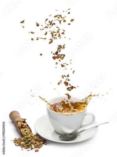 cup of tea with tea mixture falling and splashing on white background Canvas Print