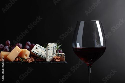 Plakat Kieliszek czerwonego wina z różnych serów, winogron i orzechów włoskich.