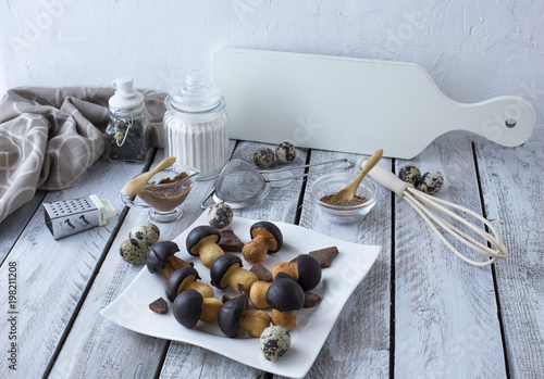 Aluminium Prints on the table, flour, eggs, chocolate and biscuits in the form of mushrooms in a white plate