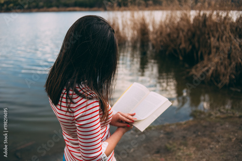 Deurstickers Young Woman Reading a Book on a Lakeside