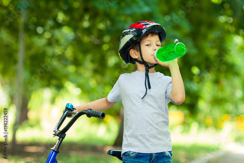 9ec356d737919 Little boy drinking water by the bike. Child in helmet riding a cycling.