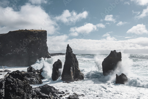 Deurstickers Water Scenic view of waves splashing on rock formations in sea against cloudy sky