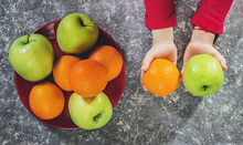 Apples And Oranges In The Hands Of A Child. Selective Focus.