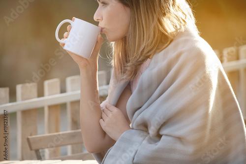 Fotografija  Woman drinking coffee in chilly morning and enjoying beautiful sunny day