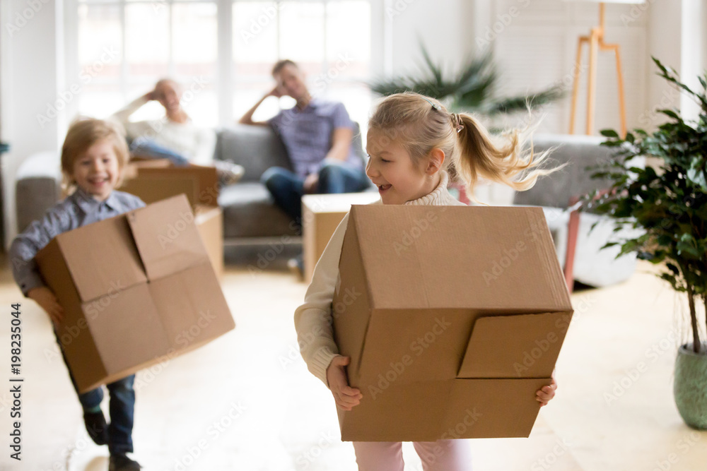 Fototapety, obrazy: Active children enjoying moving day running carrying boxes, excited kids laughing playing in new home while parents take break to rest, happy girl and boy have fun together, family relocation concept