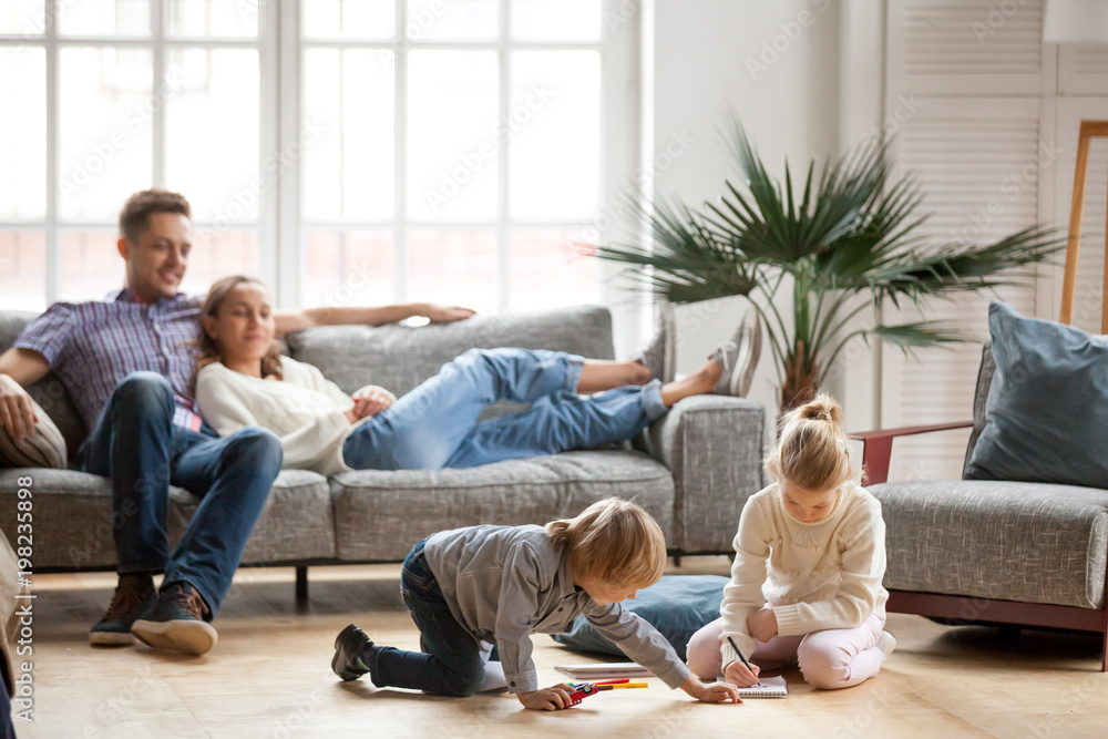 Fototapety, obrazy: Children sister and brother playing drawing together on floor while young parents relaxing at home on sofa, little boy girl having fun, friendship between siblings, family leisure time in living room