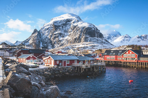 Beautiful super wide-angle winter snowy view of fishing village A, Norway, Lofoten Islands, with skyline, mountains, famous fishing village with red fishing cabins, Moskenesoya, Nordland