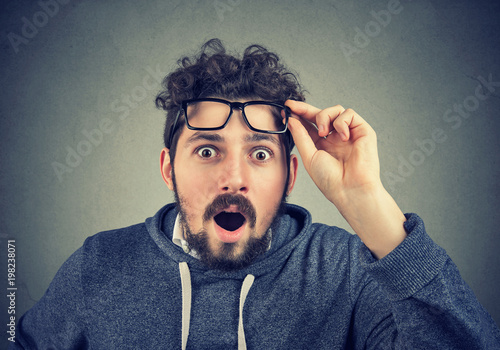 Shocked man taking off eyeglasses Canvas Print