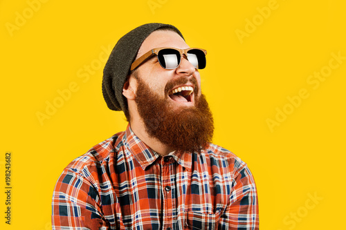 Fotografía  Portrait of young hipster man in sunglasses and hat posing on yellow background