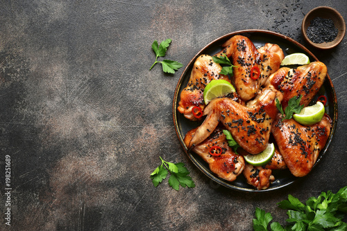 Grilled teriyaki chicken wings with black sesame and lime.Top view with copy space.