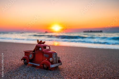 Plakat Wschód słońca na plaży tropikalnej wyspy i miniatura samochodu ciężarowego. Koncepcja podróży.