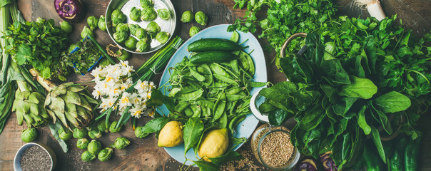 Spring healthy vegan food cooking ingredients. Flat-lay of vegetables, fruit, seeds, sprouts, flowers, greens over wooden background, top view, wide composition. Diet, clean eating food concept