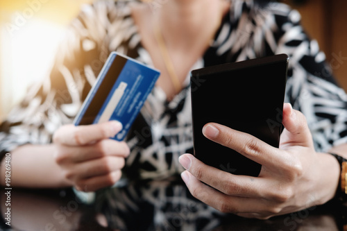 Fototapeta Online payment,Young Woman's using smart phone and holding credit card for online shopping. obraz na płótnie
