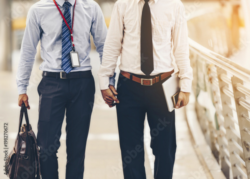 Fotomural  Two Asian business men are walking hand in hand and taking care of each other
