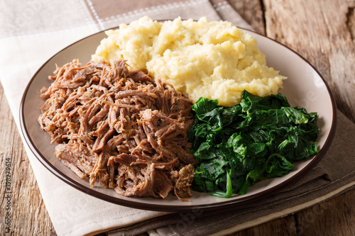 Botswana festive meal: seswaa stewed beef with pap porridge and spinach close-up on a plate. horizontal
