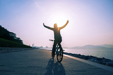 Happy Woman Cyclist Riding Bike On Sunrise Coast