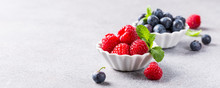 Fresh Ripe Raspberries And Bluebetties In White Bowls On Light Gray Concrete Background. Healthy Food Concept With Copy Space. Banner.