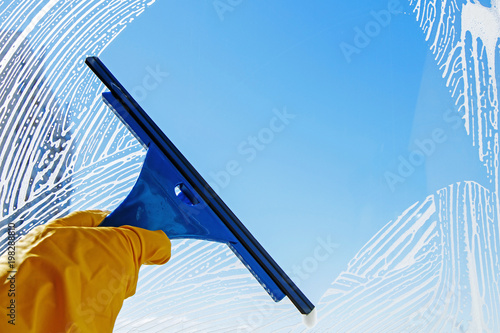 Squeegee wipe the glass with soap foam