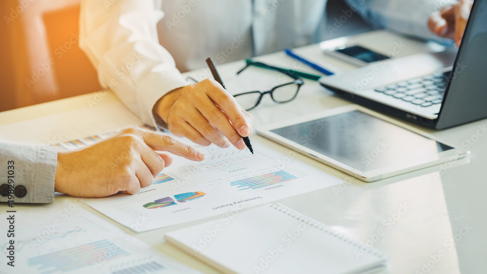 Fototapeta Two businessman investment consultant analyzing company financial report balance sheet statement working with documents graphs. Concept picture for stock market, office, tax, and project.