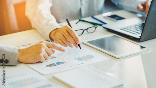 Foto  Two businessman investment consultant analyzing company financial report balance sheet statement working with documents graphs