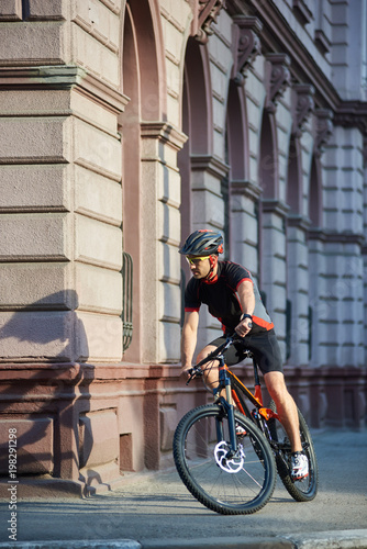 Sportsman in professional cycling clothes and protective helmet riding  along old historical city streets 2c4bc8225