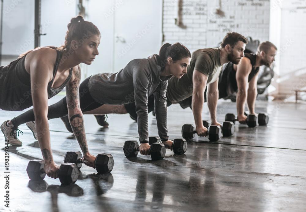 Fototapety, obrazy: Sportspeople Doing Pushups at Gym