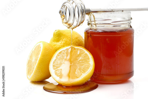 A glass of honey with dipper and lemon on a white background Canvas Print