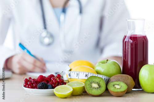 Fototapeta Some fruits such as apples, kiwis, lemons and berries on nutritionist table. obraz