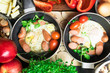 English breakfast for two. Fried eggs with sausages in a frying pan with spices and fresh vegetables.