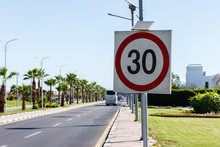Speed Limit Sign With Solar Panel In The Road With Palm Tree On A Summer Day. The Speed Limit Is 30 Km/h On A Gravel Road