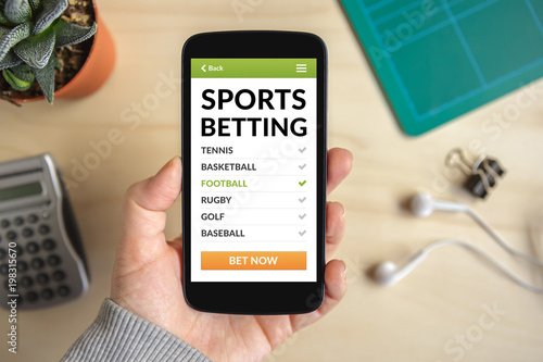 Fotografie, Obraz  Hand holding smart phone with sports betting concept on screen