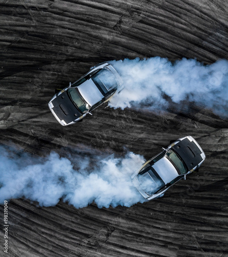 Photo Top view two drifting car on asphalt street road texture and background, Aerial view professional adrenaline driver acceleration drifting car on race track, Automobile and automotive concept