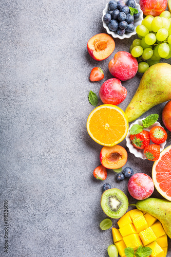 Poster Fruits Fresh assorted fruits and berries on light gray background. Colorful clean and healthy eating. Detox food. Copy space. Top view.