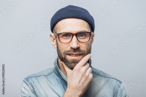 Photo  Confident satisfied bearded male keeps hand on chin, listens attentively interlocutor, wears fashionable clothing, isolated over white studio background