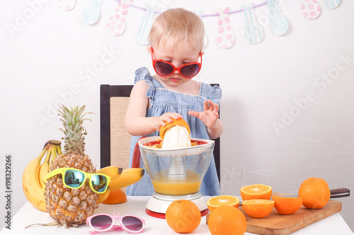 Photo Healthy food: A little girl makes fresh orange juice.