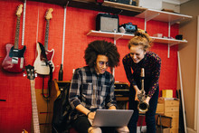 Woman With Saxophone Looking At Man Using Laptop While Practicing At Recording Studio