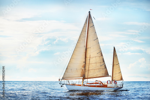 Photo Stands Ship Vintage wooden two mast yacht (yawl) sailing in a open sea on a clear day. The gulf of Riga